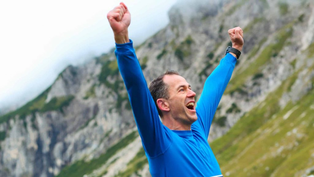 excited man reaching new record high on mountain side
