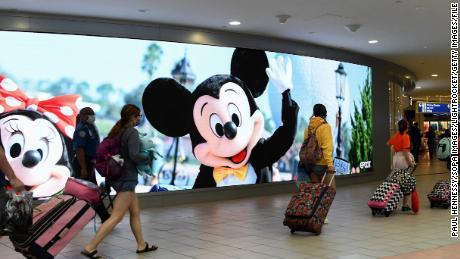 Wisatawan melewati papan iklan Walt Disney World di Bandara Internasional Orlando saat akhir pekan 4 Juli dimulai, pada 2 Juli 2021.