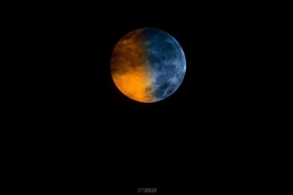 Bulan purnama berwarna setengah biru dan setengah oranye.