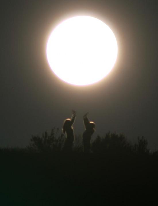 Dua orang yang berdiri saling berhadapan sedang menuju bulan purnama besar yang terbuka.