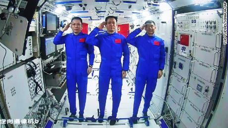 Astronot China, dari kiri Tang Hongbo, Ni Haisheng dan Liu Beoming memberi hormat dari atas modul inti Stasiun Luar Angkasa China pada 23 Juni.