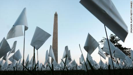 """& quot;  Di Amerika: Ingat """"  Sebuah instalasi seni publik di Washington, D.C., memperingati semua orang Amerika yang meninggal karena Covid-19.  Pada tanggal 18 September, ada lebih dari 660.000 bendera plastik kecil di lokasi tersebut, beberapa dengan pesan pribadi untuk mereka yang meninggal."""